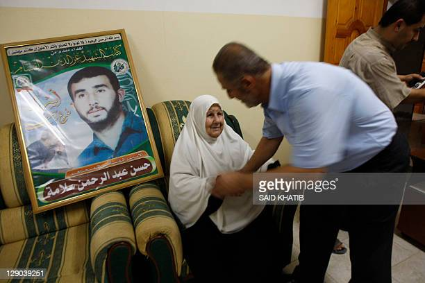 The Family of Hassan Salame watch a television broadcasting the speech of Hamas leader Khaled Meshaa celebrating a deal that will see Palestinian...