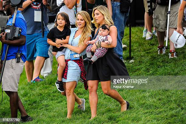 The family of Jason Day of Australia from right wife Ellie daughter Lucy and son Dash come out to the 18th hole green following his victory during...