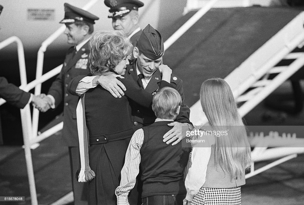The family of Major Wesley D. Schierman, USAF, from Spokane, Washington, embrace him as he exits a plane at Travis Air Force Base. Schierman had been a POW since his F-105 jet was shot down over North Vietnam on August 28, 1965.