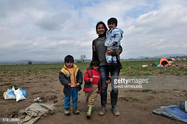 The family of Mohamed Ibrahim pose as they travel to meet him in Switzerland on March 17 2016 at a makeshift camp at the GreekMacedonian border near...