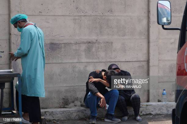 The family of one of a fire victims mourns while sitting in front of the prison in Tangerang on September 8 after a prison fire broke out and killed...