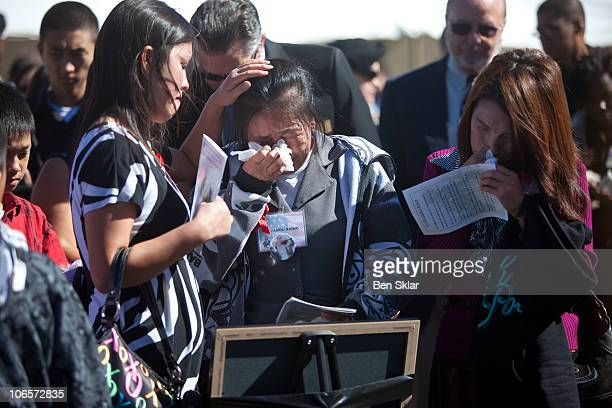 The family of Spc Kham Xiong including his mother Panou Xiong center grieve at a remembrance service recognizing the 13 victims killed in the Ft Hood...