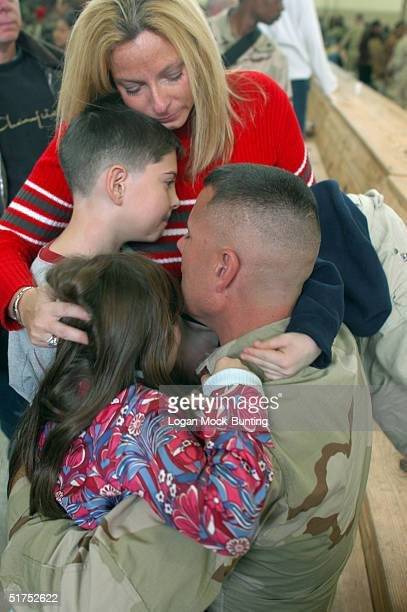 The family of US Army Captain Kelly Cole hugs his family before he is deployed from Pope Air Force Base in Fort Bragg November 16 2004 North Carolina...