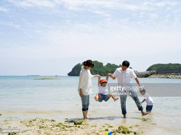 the family playing on the beach - 休日 ストックフォトと画像