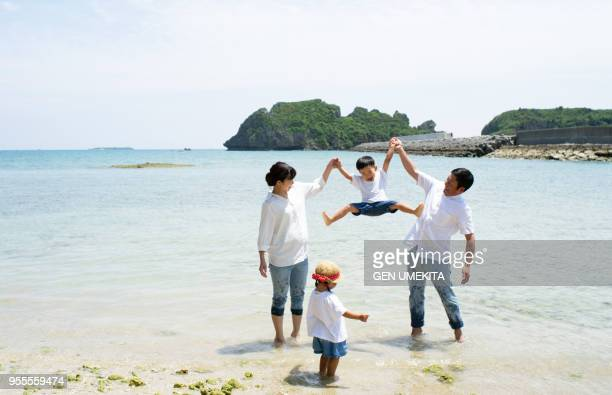 the family playing on the beach - 4人 ストックフォトと画像