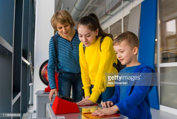 The family, the mature woman and kids, teenager girl and little boy, exploring bio electricity and electromagnetic induction in the Hall of Science