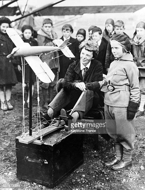 The famous American aviator Amelia Earhart crossed the Atlantic and explains to children with a reduced model the operation of the catapult to launch...
