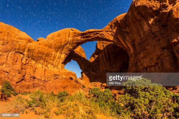 The famous and photogenic Double Arch at Arches National Park in Utah shot in moonlight with illumination from a rising waning gibbous Moon on April...