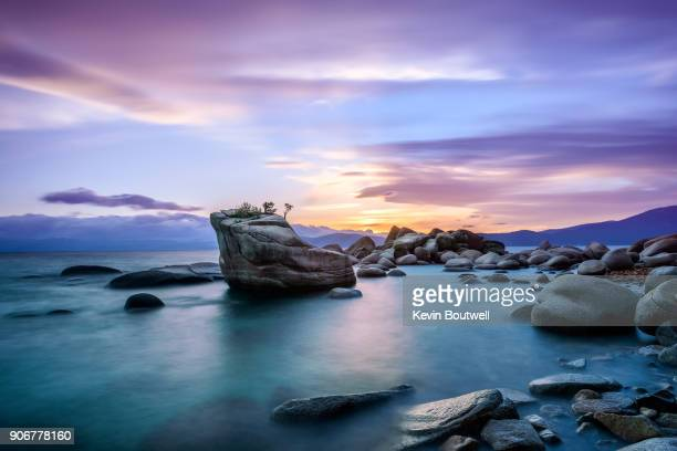 the famous bonsai rock in lake tahoe at sunset - lake tahoe stock photos and pictures