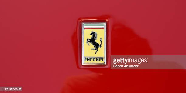 The famous Ferrari prancing horse logo embellishes the hood of a red Ferrari on display at a Fourth of July classic car show in Santa Fe, New Mexico.