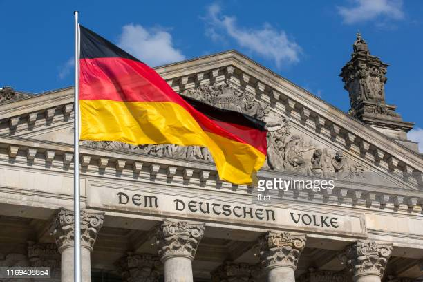 "the famous inscription on the architrave on the west portal of the reichstag building in berlin: ""dem deutschen volke"" with german flag - german flag stock pictures, royalty-free photos & images"