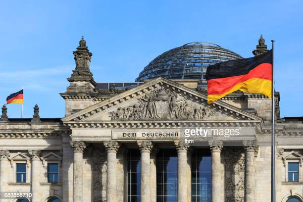 """The famous inscription on the architrave on the west portal of the Reichstag building in Berlin: """"Dem Deutschen Volke"""" with german flag"""