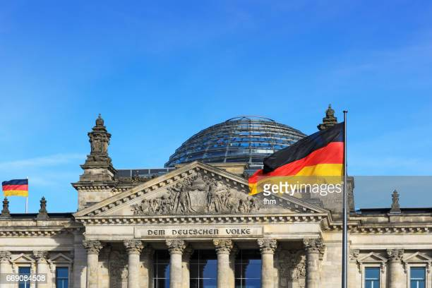 The famous inscription on the architrave on the west portal of the Reichstag building in Berlin: 'Dem Deutschen Volke' with german flags