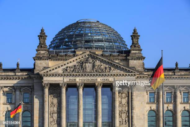 "the famous inscription on the architrave on the west portal of the reichstag building in berlin: ""dem deutschen volke"" with german flag (berlin, germany) - bundestag stock pictures, royalty-free photos & images"