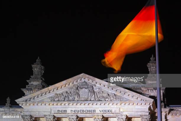 The famous inscription on the architrave on the west portal of the Reichstag building in Berlin: 'Dem Deutschen Volke' with german flag at night (Berlin, Germany)