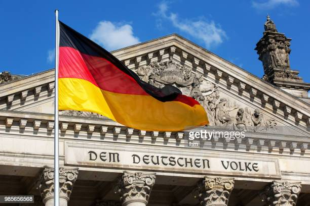 The famous inscription on the architrave on the west portal of the Reichstag building in Berlin: 'Dem Deutschen Volke' with german flag