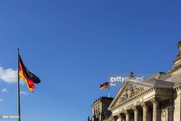 The famous inscription on the architrave on the west portal of the Reichstag building in Berlin: 'Dem Deutschen Volke' with german flags (Berlin, Germany)