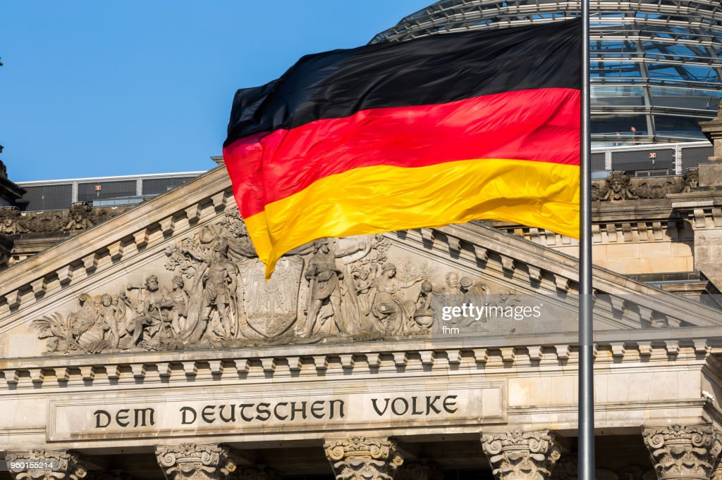 """The famous inscriptionon the west portal of the Reichstag building in Berlin: """"Dem Deutschen Volke"""" with german flag : Stock-Foto"""