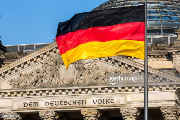 "the famous inscriptionon the west portal of the reichstag building in berlin: ""dem deutschen volke"" with german flag - bundestag stock photos and pictures"