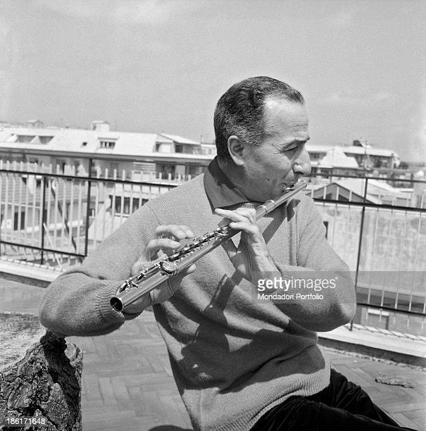 The famous Italian flute player Severino Gazzelloni is seated on the terrace of his flat in Rome and is playing his gold flute produced in Boston in...
