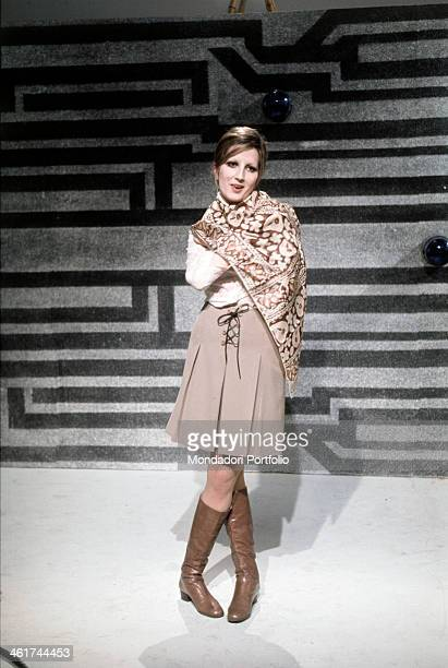 The famous Italian singer Mina portrayed into a TV studio wearing an elegant brown suit and a foulard on her shoulders at the backs of the young...
