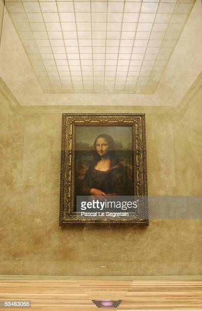 The famous Leonardo Da Vinci painting The Mona Lisa is seen on display in the Grande Galerie of the Louvre museum on August 24 2005 in Paris France...