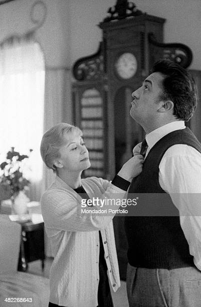 The famous movie director Federico Fellini in the sunny living room of his home grimaces and turns his eyes to the ceiling while his beloved wife and...