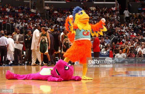 The Famous San Diego Chicken celebrates after knocking down Barney the Dinosaur during a break in the game between the Los Angeles Clippers and the...