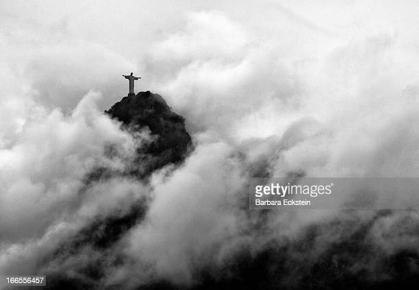 The famous statute of Jesus Christ stands on top of Corcovado overlooking Rio de Janeiro surrounded by clouds and fog. This dramatic black and white...