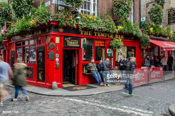 the famous temple bar in dublin during day of autumn with people walking in street - temple bar dublin stock photos and pictures