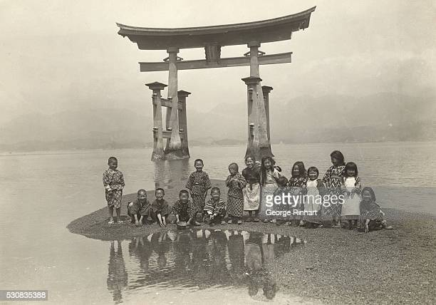 The famous Torii of the Inland Sea with a gleeful group of Japanese children on a strip of sand near its' base is shown