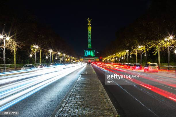 The famous victory column (Siegessäule) in the german capital Berlin in special illumination during a annual public light event and with passing cars at night