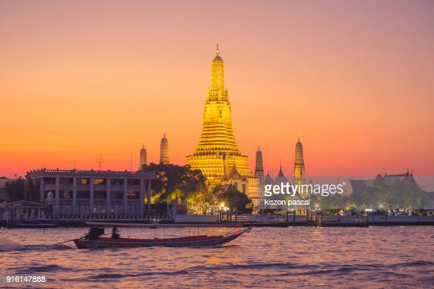 the famous Wat Arun buddhist temple in Bangkok during sunset , Thailand