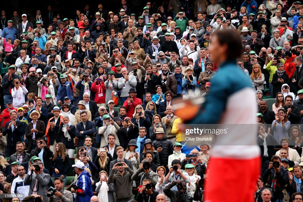 The fans applaud Rafael Nadal of Spain as he celebrates victory with the Coupe des Mousquetaires trophy in the men's singles final against David Ferrer of Spain during day fifteen of the French Open at Roland Garros on June 9, 2013 in Paris, France.