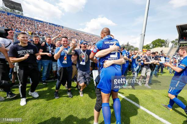The fans cheer with David Pisot of Karlsruhe during the 3. Liga match between Karlsruher SC and Hallescher FC at Wildparkstadion on May 18, 2019 in...
