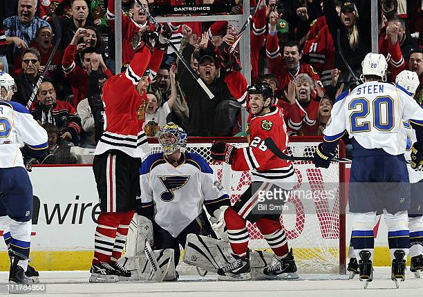 The fans go wild as Fernando Pisani and Jake Dowell of the Chicago Blackhawks react in front of St. Louis Blues goalie Ty Conklin after the...