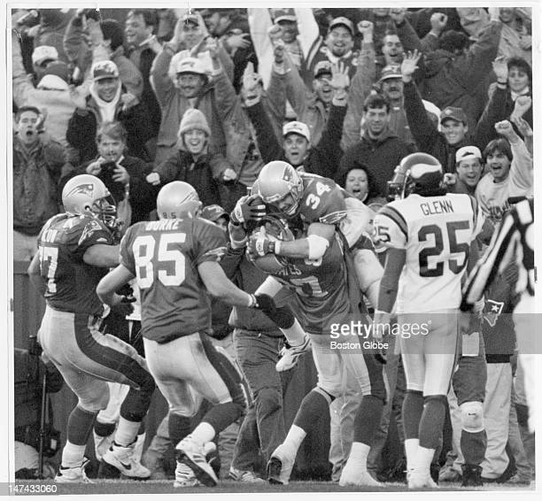 The fans go wild as Patriots Kevin Turner gets hoisted triumphantly by teammate Ben Coates following Turner's overtime reception of a Drew Bledsoe...