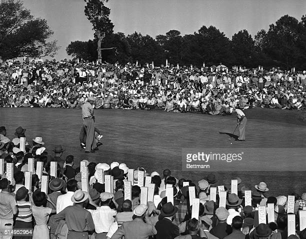 The fans many armed with periscopes watch as Ben Hogan sinks his final putt for a 69 and a 72hole total of 274 winning the Masters golf tournament by...