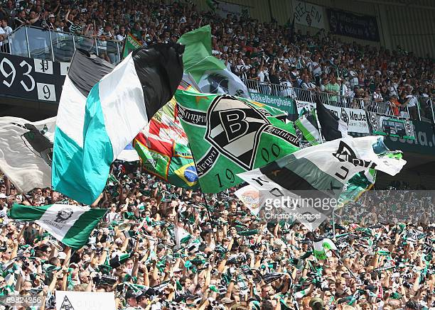 The fans of Gladbach wave flags during the Bundesliga match between Borussia Moenchengladbach and Hertha BSC Berlin at the Borussia Park on August...