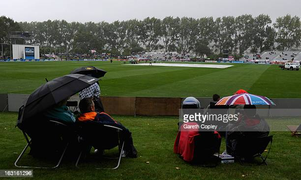 The fans shelter from the rain as it delays the start of play during day one of the First Test match between New Zealand and England at University...