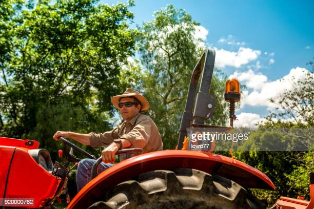 The farmer cultivates his farm with a tractor
