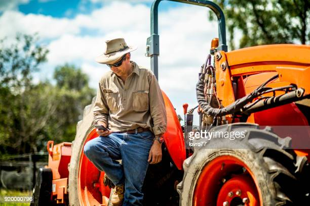 The farmer stands beside his tractor and looks at the phone