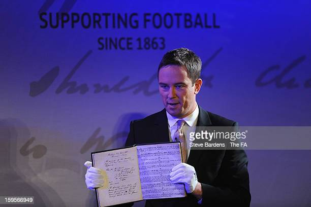 The FA's 1863 Minute Book is held by presenter Simon Thomas during the official launch to mark the FA's 150th Anniversary Year at the Grand Connaught...