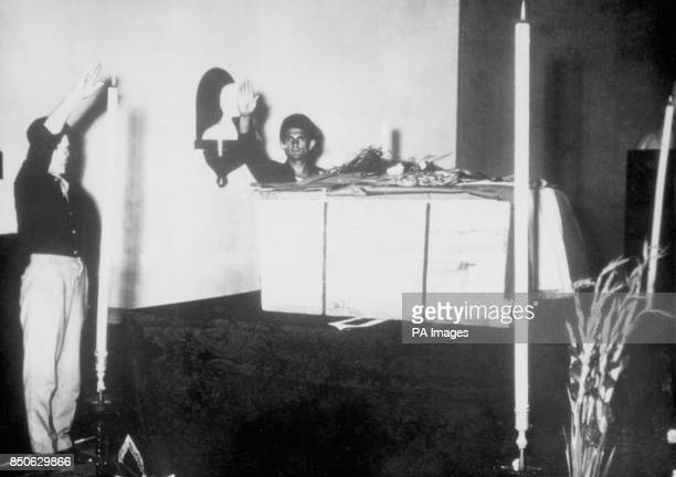 The Fascist salute is given beside the plain wooden packing case containing the remains of Benito Mussolini the former dictator of fascist Italy in a...