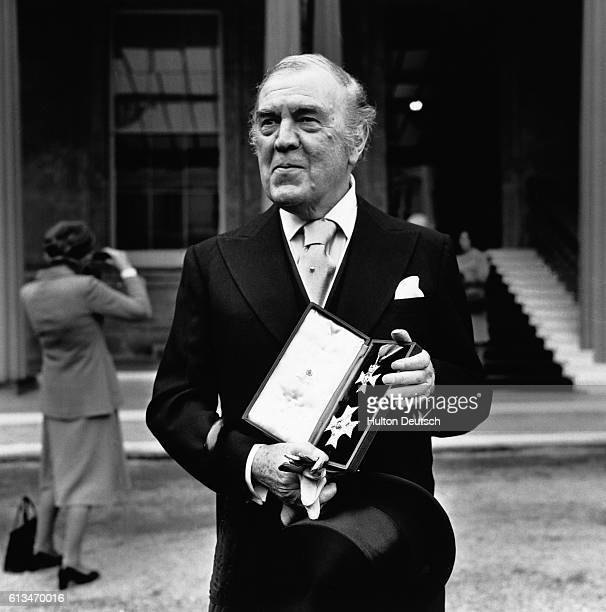 The fashion designer and Royal dressmaker Norman Hartnell outside Buckingham Palace, after reciving his knighthood from the Queen. He displays the...