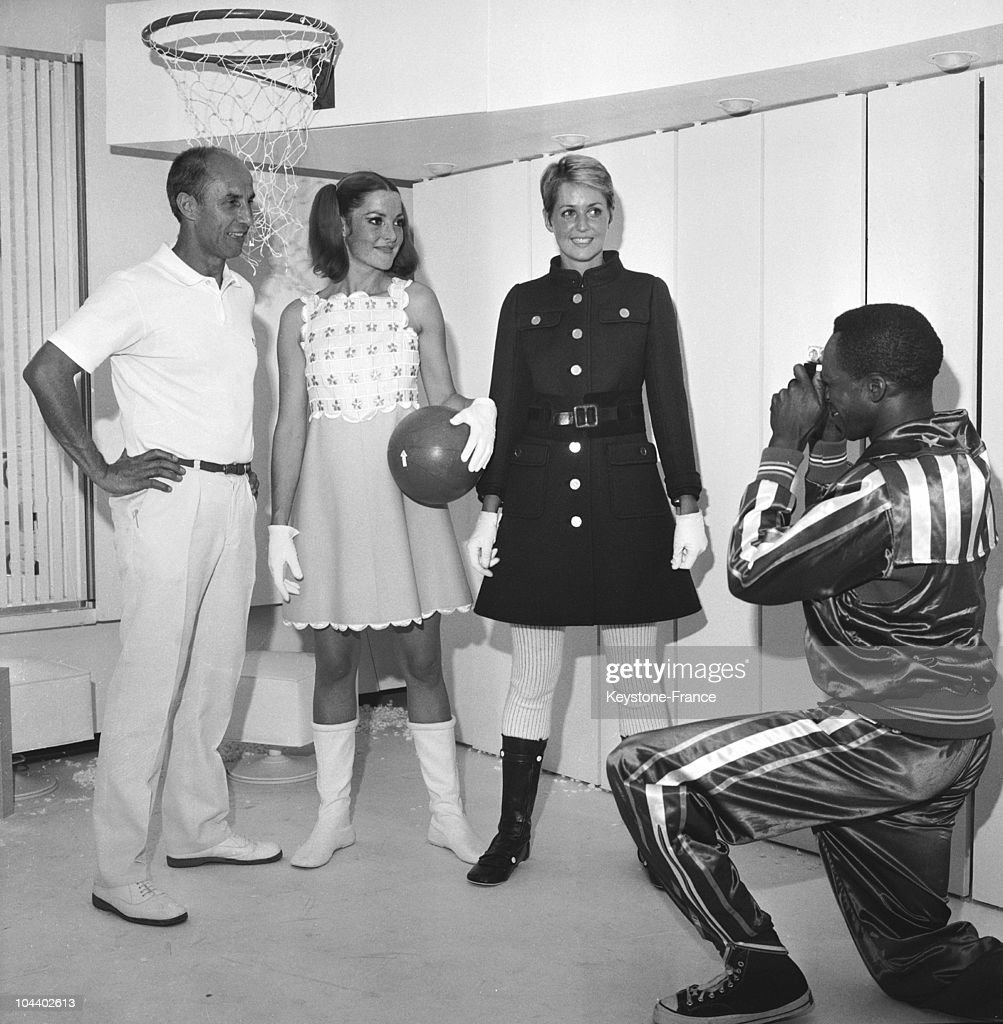 The fashion designer Andre COURREGES posed with two of his models : one wears a short, yellow and white cotton dress, the other a blue wool coat with golden buttons.