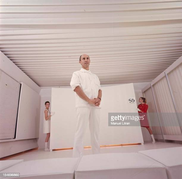 The fashion designer Andre Courreges standing in an ultramodern white lounge presenting two new models to its collection after years of silence