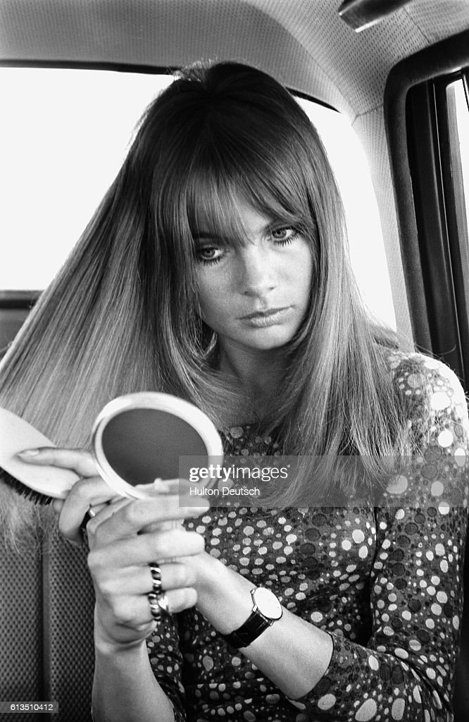 The fashion model Jean Shrimpton brushes her hair whilst in a car, 1966.