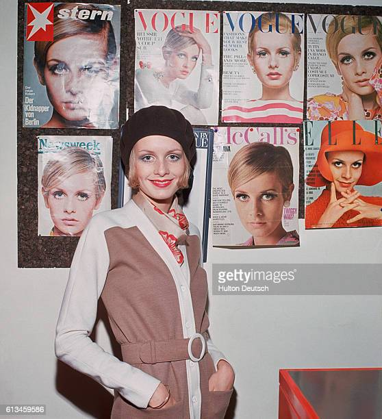 The fashion model Twiggy poses beside a display of magazine covers for which she has modeled