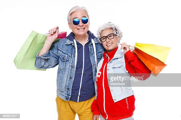 The fashion of the elderly couple with shopping bags